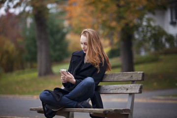 Young woman sitting on bench and using mobile phone