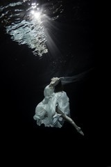 Young female ballet dancer dancing underwater