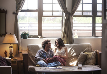 Couple sitting on sofa at home