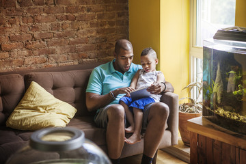 Father showing tablet computer to his son at home