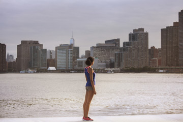Woman standing on riverbank looking at skyline