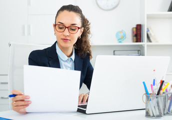 Smiling woman working with paperwork and laptop