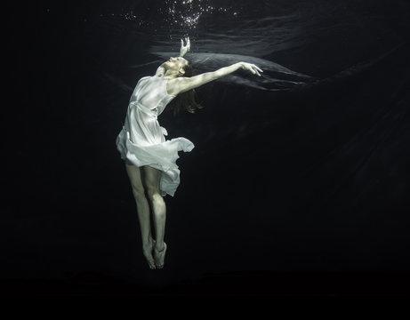 Young female ballet dancer dancing underwater