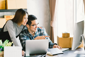 Young Asian couple startup family business, online marketing packaging and delivery scene. SME entrepreneur, business partner, or freelance work at home concept