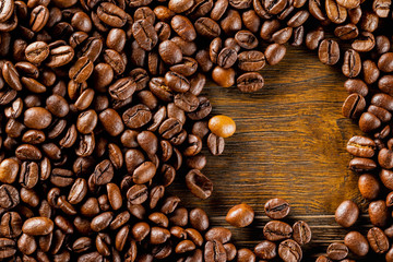 Macro image of roasted coffee beans at brown textured wooden board background.