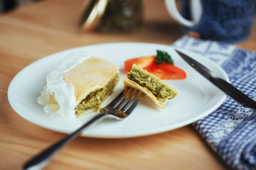 pie with spinach and tomato slice on wooden table.