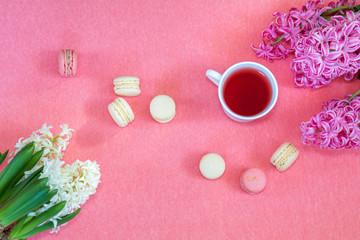Beautiful spring holiday background. Cup of tea, fresh white and pink hyacinth and sweet  berry and vanilla macaroons cookies on pink copy space groundwork.