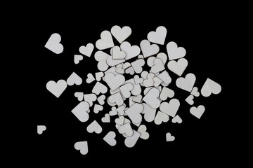 A pile of wooden hearts of various sizes on a black background