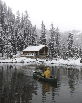 Person canoeing towards wood cabin in snow