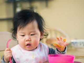 baby girl eating mashed sweet potatoes