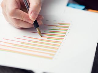 Business man hold a pen on bat chart