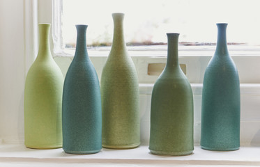 Green and Turquoise bottles on a windowsill