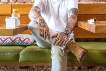 Man sitting in cafe with tattooed arms and hands, mid section