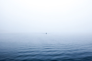 Boat in distance, traveling on calm water