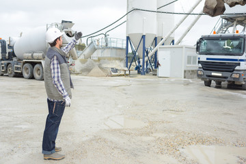 worker directing lorry in silo