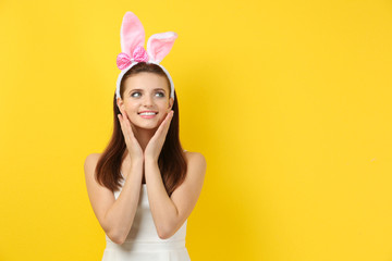 Beautiful girl with bunny ears on color background
