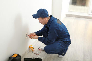 Electrician measuring voltage of socket in new building