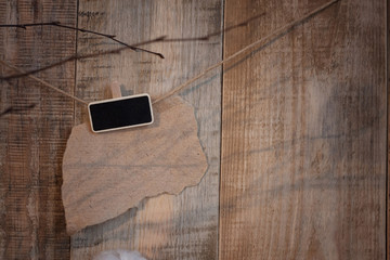 Rustic wooden abstract universal background. Shadow of branch against the wall with a clothespin with empty space for writing on craft paper. Clothespin with a black plate with copy space for writing.