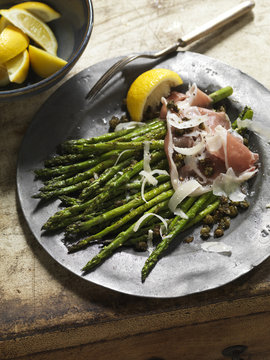 Dish of grilled asparagus, prosciutto and lemon
