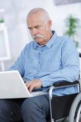 disabled senior man sitting in wheelchair using laptop