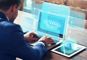 Business, technology, internet and networking concept. Young businessman working on his laptop in the office, select the icon Internal audit on the virtual display.