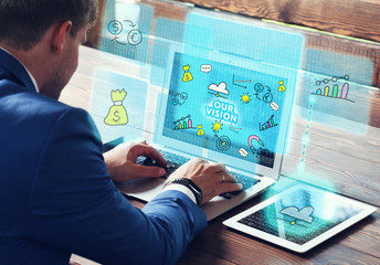 Business, technology, internet and networking concept. Young businessman working on his laptop in the office, select the icon Our vision on the virtual display.