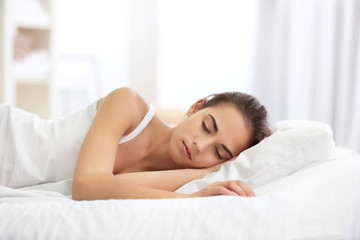 Depressed young woman lying on bed at home