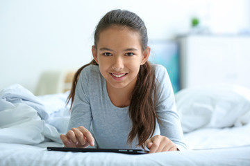 Cute girl lying on bed with tablet computer
