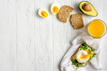 sandwich with poached eggs on wooden background top view mockup