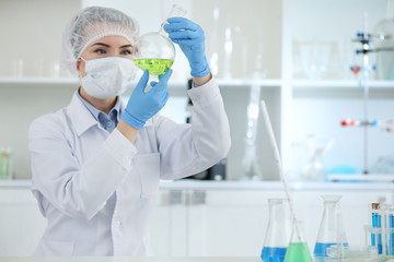 Scientist holding test flask with sample in laboratory