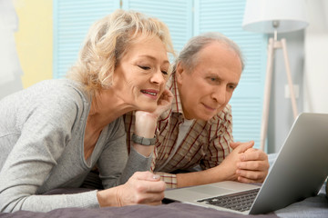 Senior couple making video call using laptop at home