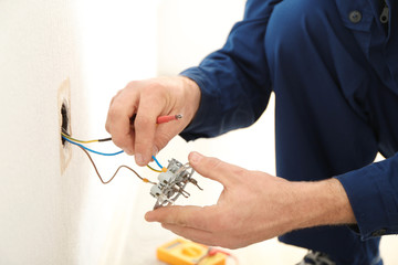 Electrician attaching wires to socket in new building, closeup