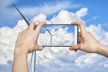 Girl taking pictures on mobile smart phone in Wind turbine power at daylight