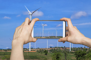 Tourist using smartphone to take a picture of  wind turbines at daylight