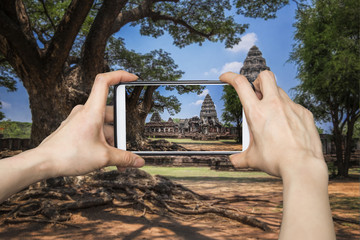 Tourist using smartphone to take a picture of  Prasat Hin Phimai in Nakonratchasima, Thailand