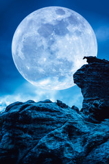 Fototapete - Boulder against blue sky with clouds and beautiful full moon at night. Outdoors.