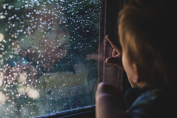 Little boy pointing on the drops on the window. Horizontal indoors shot.