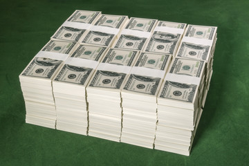 Stacks of one million US dollars in hundred dollar banknotes on green table