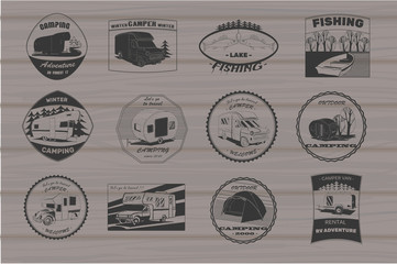 vintage camping and outdoor adventure emblems, logos and badges. Camping equipment. Camp trailer in the forest on wood background.