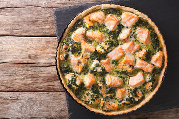 Tasty Savory Tart with salmon and spinach in the dish for baking close-up. horizontal top view