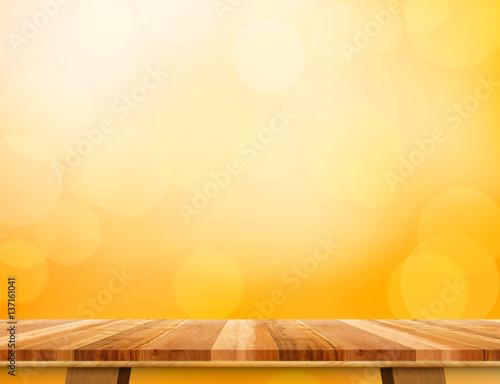 empty brown wood table top at orange bokeh light background mockup