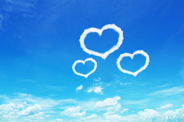 three heart shaped clouds on blue sky for design