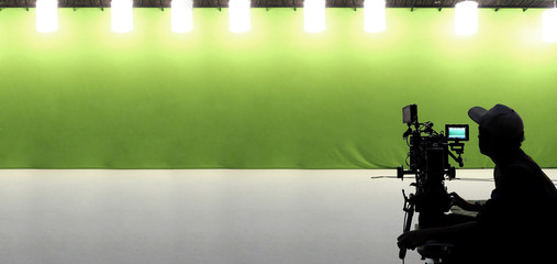 Silhouette of camera man with his professional video kit such as high definition lens equipment, tripod, rig, gimbal, LED monitor and green screen for chroma key technique in studio panorama view.