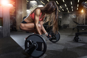 Sexual young girl preparing for the exercises with barbell in gym