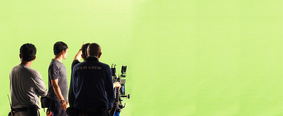 Behind the scenes of TV commercial movie film or video shooting production which crew team and photographer camera man setting up green screen for chroma key technique in big studio panorama view.