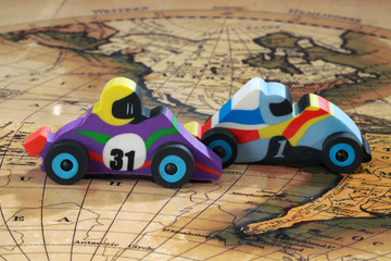 Toy cars drive on a geographic map