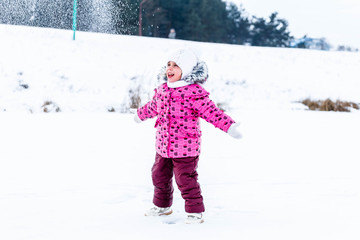 Little girl throwing snow in the winter in nature