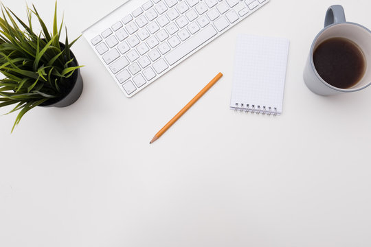 Minimal office white desk with plant and coffee