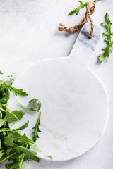 Background with green fresh rucola and marble cutting board on light gray stone table. Healthy food concept with copy space. Top view.