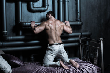Young healthy handsome attractive sexy bodybuilder poses on a purple bed demonstrating muscular back